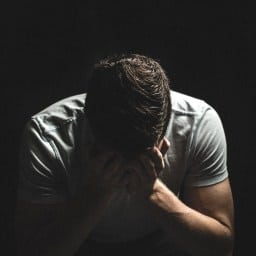 A man is experiencing a panic attack and has his head in his hands. He is thinking about reaching out to an online anxiety counselor | Online Therapy for Anxiety | Synergy eTherapy