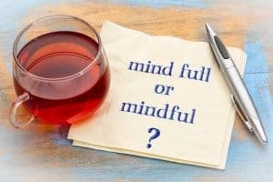 "Photo of a cup of tea, a pen and a napkin that says, ""mind full or mindful?"" Representing the benefits of online mindfulness training in WI 