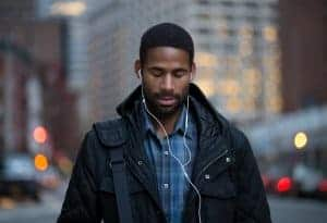 Young african american man walking with headphones in while zoning out | online therapy for anxiety treatment for teens & adults | Synergy eTherapy