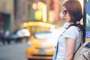 Young woman leaning against a bus stop in a large city | Online Therapy in NY | Synergy eTherapy