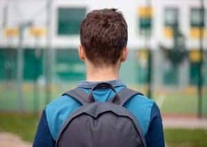 College student walking with a backpack. He experiences anxiety related to school and the pressure to perform well. He is on his way to attend an online therapy session.
