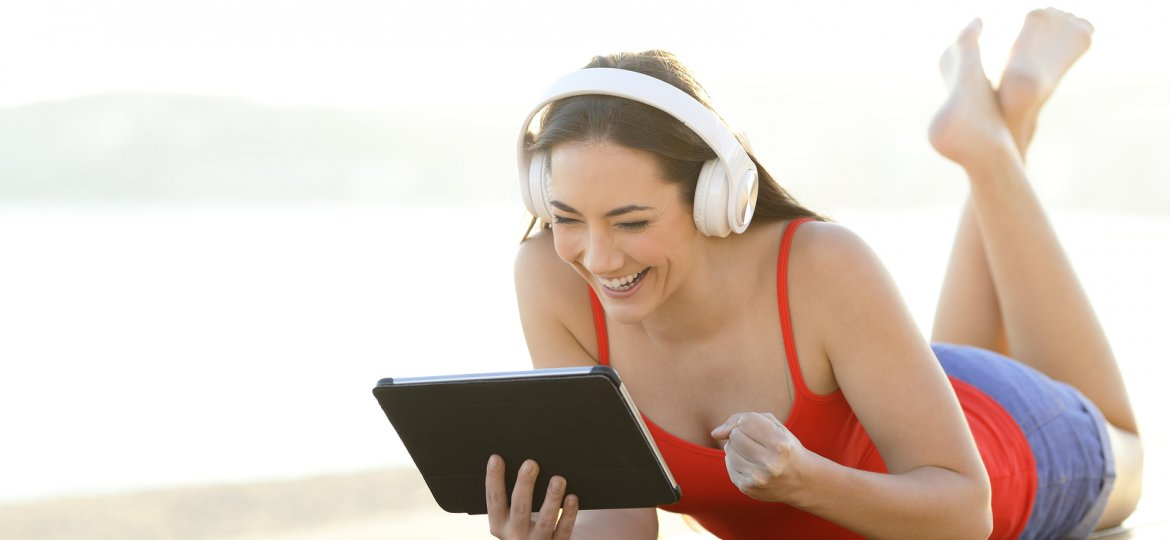 teenage girl wearing headphones watching a video on a tablet on the beach | Online Counseling in Florida | Synergy eTherapy