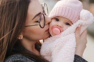 Mom kissing baby outside in Chicago, IL | Online Therapy in Illinois | Synergy eTherapy