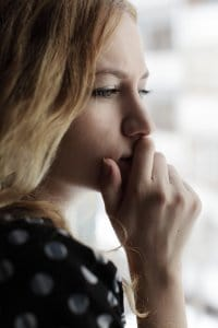 Sad woman looking out the window with her hand over her mouth before attending online therapy for trauma with synergy eTherapy in the state of Kansas.