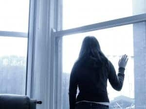 woman with bipolar depression stares out the window. She receives online depression treatment and online counseling with synergy etherapy an online counseling practice