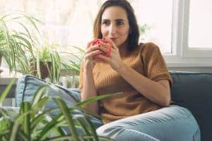 depressed woman finds relief from the symptoms of depression and sits on the couch with coffee. She had online depression treatment with synergy etherapy an online counseling practice.