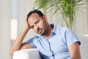 depressed man at home before meeting with a Synergy eTherapy therapist for online depression treatment and counseling