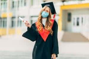 Happy graduate wearing a mask. She meets with an online therapist to get help dealing with grief. Learn more about online grief counseling from Synergy ETherapy here!