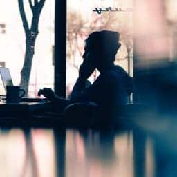 Man sitting in an ecafe distressed. He gets online therapy for grief and loss with synergy etherapy