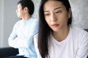 unhappy asian couple gets online marriage counseling with a Synergy eTehrapist. Begin online couples therapy.