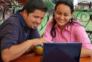 young hispanic couple on the computer meeting with a synergy eTherapist for online couples therapy in the united states. Contact synergy eTherapy for online relationship therapy